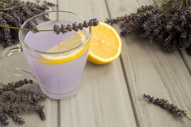 Lavendel-tee mit zitrone auf dem grauen hölzernen hintergrund