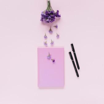 Lavendel über dem geschlossenen notizbuch und zwei filzstifte auf rosa hintergrund