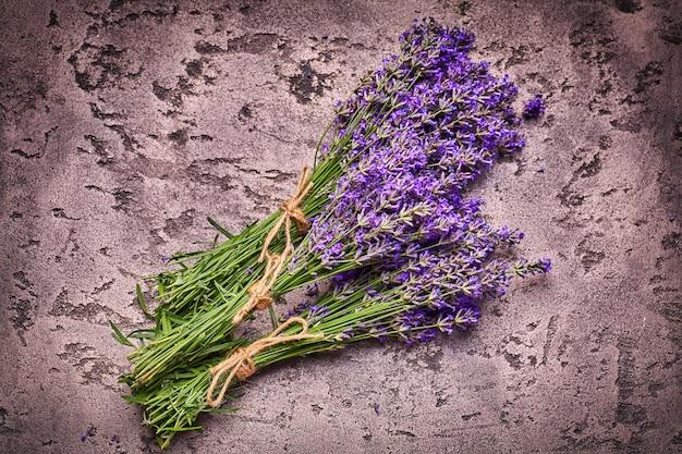 Lavendelblüten auf grauem betonhintergrund mit kratzern
