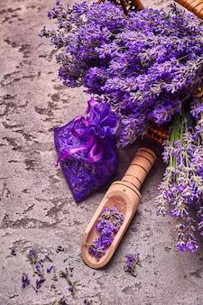 Lavendelblüten in korb und aromatischer tasche auf grauem betonhintergrund. ansicht von oben.
