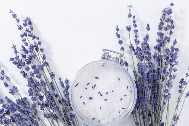 Lavendelblüten und glas mit meersalz. badekurorthintergrund mit exemplarplatz. tiefenschärfe.