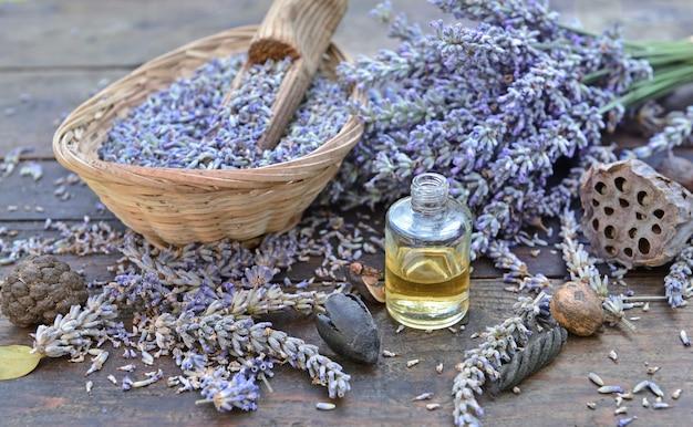 Lavendelblütenblätter in einem kleinen korb mit einer flasche ätherisches öl auf einem holztisch