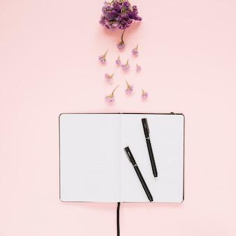Lavendelblumen über dem geöffneten buch und zwei filzstifte auf farbigem hintergrund