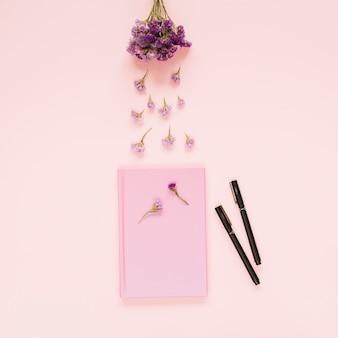 Lavendelblumen über dem rosa buch und zwei filzstifte auf farbigem hintergrund
