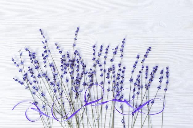 Lavendelblumen und -band auf weißem hölzernem