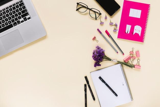 Lavendelblumenbündel mit schreibwaren und laptop auf beige hintergrund