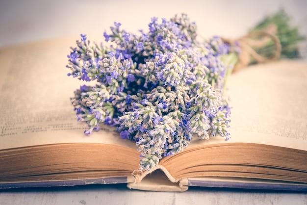 Lavendelblumenstrauß gelegt über ein altes buch auf einem weißen hölzernen
