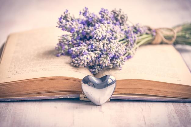 Lavendelblumenstrauß gelegt über ein altes buch auf einen weißen hölzernen hintergrund.