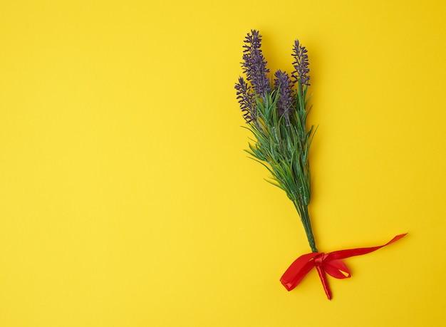 Lavendelblumenstrauß und rotes band auf einer gelben oberfläche