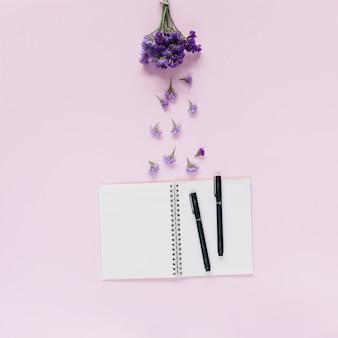 Lavendelbündel über dem offenen notizbuch mit zwei filzstiften auf rosa hintergrund
