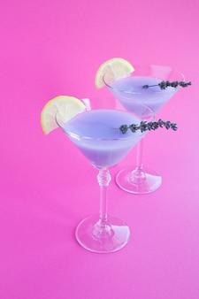 Lavendelgetränk mit zitrone in martini-gläsern auf rosa.