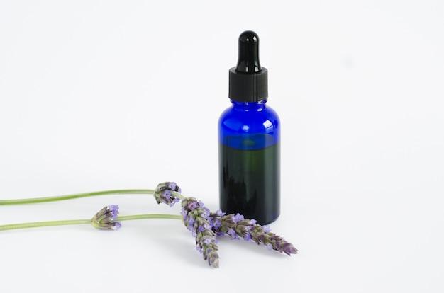 Lavendelöl. blumen und flasche mit pipette auf weißer oberfläche