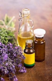 Lavendelöl mit frischem lavendel auf einer holzoberfläche