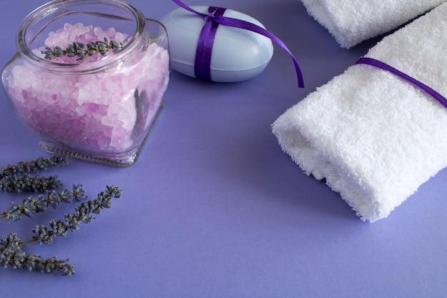 Lavendelsalz, seife und weiße handtücher auf dem violetten hintergrund