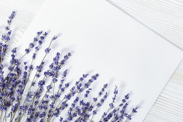 Lavendelzweige auf holz und papier für ihren text. lavendelblumen auf weißem hölzernem hintergrund mit kopienraum.