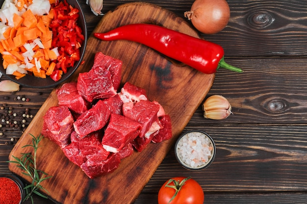 Layout der zutaten zum kochen von gulasch oder eintopf. rohes rindfleisch, gemüse, gewürze, auf rustikalem holztisch