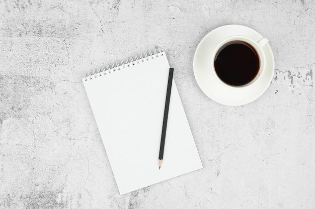 Layout des tagesplans. notizblock, bleistift und tasse kaffee. draufsicht