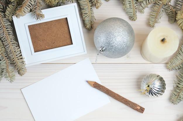 Layout eines fotorahmens, papiers, bleistifts auf einem weihnachtsthema auf einem weißen holztisch