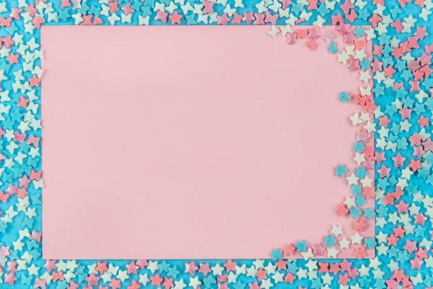 Layout für die aufnahme. rosa blatt für das schreiben auf einen blauen hintergrund mit dekorativen mehrfarbigen elementen mit sternen und bögen. flachgelegt, draufsicht