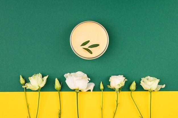 Layout von blumen und naturcreme. auf einem gelbgrünen hintergrund. offene und geschlossene knospen, platz für eine inschrift. flach liegen.