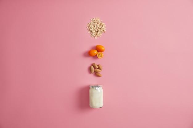 Layout von frischem joghurt mit nüssen, cumquat und hafer, um köstliches haferflocken zuzubereiten