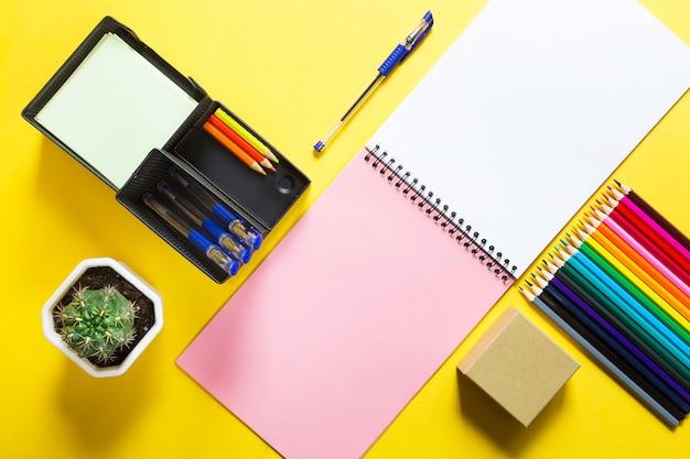 Layout von mehrfarbigem briefpapier auf einem gelben hintergrundspiralheft, buntstiften, geschäftsflachlage