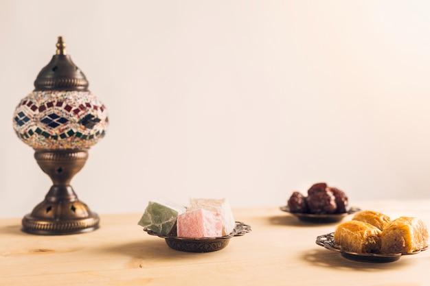 Layout von pflaumen in der nähe von baklava und türkischen köstlichkeiten auf untertassen