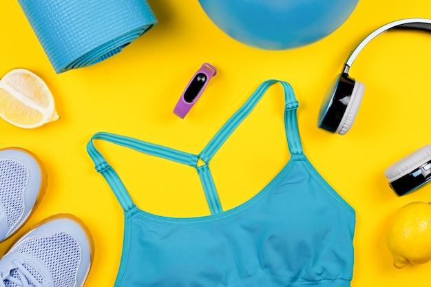 Layout von sportkleidung und accessoires für frauen auf gelb