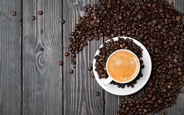 Layout, weiße tasse mit espressokaffee und körnern auf einem dunklen holztisch
