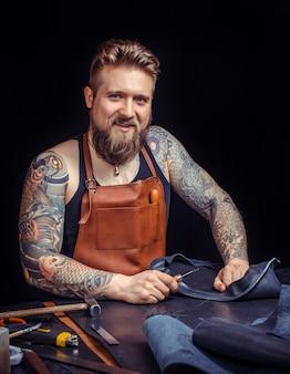 Leather artist verarbeitet im lederstudio ein werkstück aus leder. / kunsthandwerker aus leder, das mit leder arbeitet.