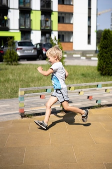 Leben der kinder in einer modernen stadt - kleiner junge hat spaß auf dem spielplatz nahe dem haus