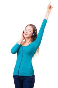 Leben im musikrhythmus! fröhliche junge frauen, die in kopfhörern stehen und lächeln, während sie vor weißem hintergrund stehen