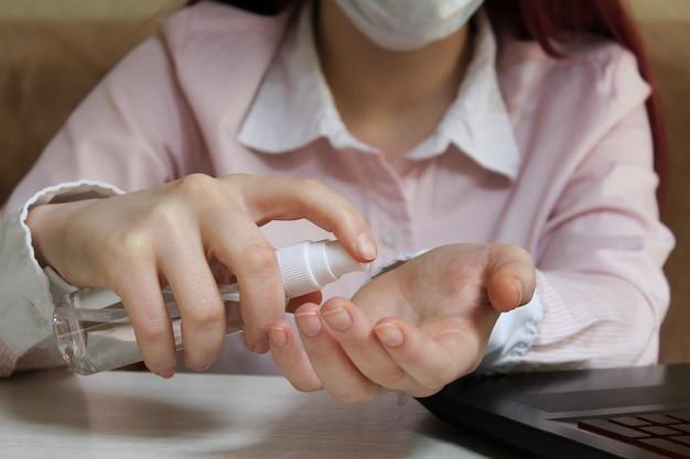 Leben im quarantäne-coronavirus. online-fernunterricht. ein schulmädchen in einer maske reinigt ihre hände mit desinfektionsgel. coronavirus-pandemie in der welt.