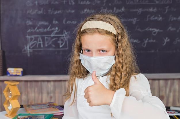 Leben während der coronavirus-pandemie. mädchen in der weißen bluse mit der medizinischen schutzmaske, die daumen oben auf tafelhintergrund zeigt.