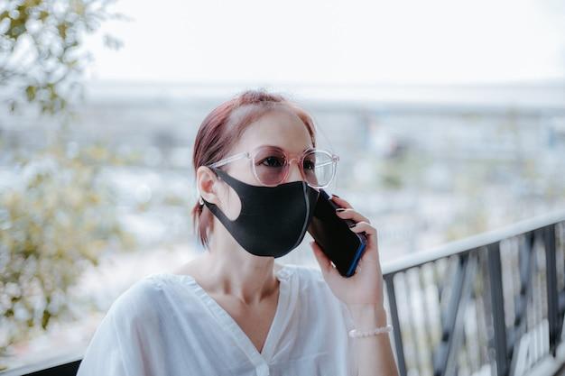 Leben während der covid-19-pandemie. asiatin benutzt smartphone mit medizinischer maske auf der stadtstraße.