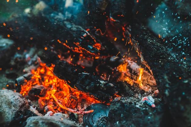 Lebendig schwelendes brennholz brannte in feuernahaufnahme. atmosphärisch mit orange flamme des lagerfeuers. vollbild des freudenfeuers mit funken im bokeh. warmer wirbel aus glühender glut und asche in der luft