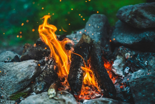 Lebendig schwelendes brennholz brannte in feuernahaufnahme. orangenflamme des lagerfeuers. vollbild des freudenfeuers mit funken im bokeh. warmer wirbel aus glühender glut und asche in der luft