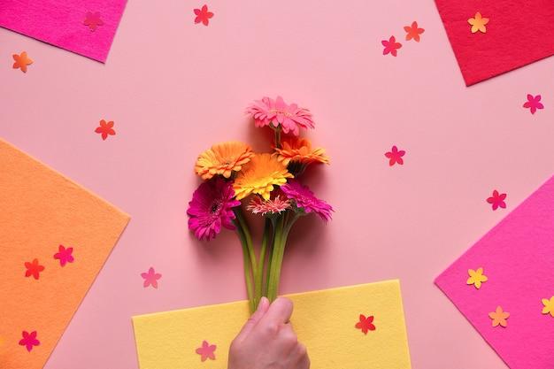 Lebendige flache lage mit der hand, die gerbera-gänseblümchenblumen auf hintergrund hält, der mit filz geschichtet wird