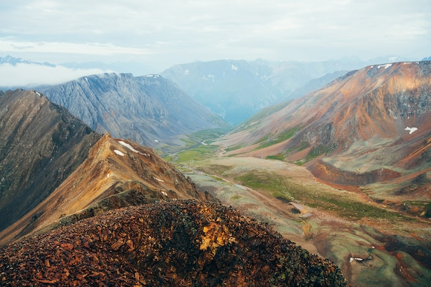 Lebendige mehrfarbige landschaft des grünen tals zwischen großen felsigen bergen.