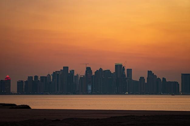 Lebendige skyline von doha bei dramatischem sonnenuntergang von der gegenüberliegenden seite der bucht der hauptstadt aus gesehen.