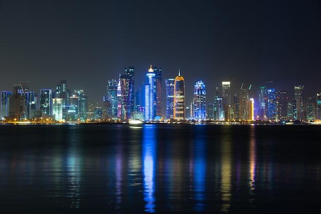 Lebendige skyline von doha bei nacht von der gegenüberliegenden seite der hauptstadtbucht bei nacht aus gesehen.