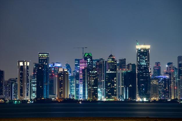 Lebendige skyline von doha bei nacht von der gegenüberliegenden seite des sonnenuntergangs in der hauptstadtbucht aus gesehen.
