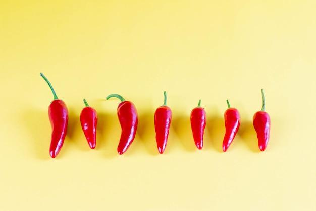Lebendiger roter chili auf gelbem hintergrund, flach liegen. rotes würziges chilischoten-tapetenmuster
