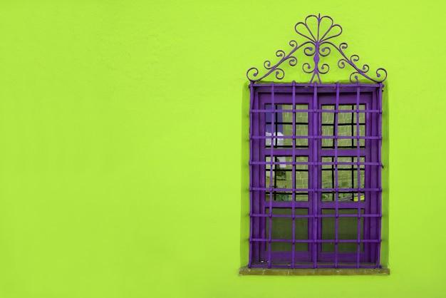 Lebendiges lila schmiedeeisenfenster auf lebendiger neongrüner rauer betonwand