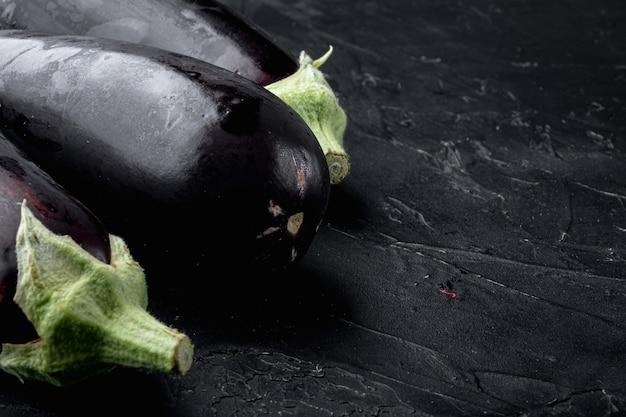 Lebendiges reflektierendes lila auberginengemüseset der aubergine auf schwarzem stein