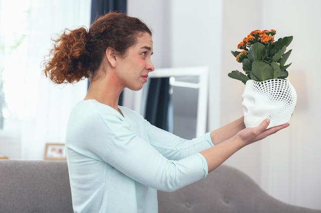 Lebensentscheidungen. junge frau, die sich entschuldigt, sich von ihren lieblingspflanzen verabschiedet zu haben, was sie zu allergischen reaktionen führt
