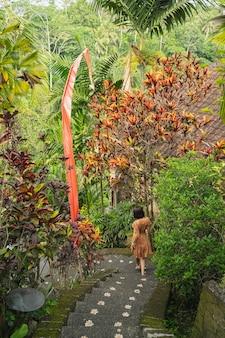Lebensfreude. entspannte brünette weibliche person, die grüne exotische pflanzen genießt und nach unten rennt, um ihre freunde zu treffen