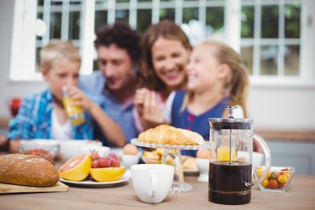 Lebensmittel auf tabelle während glückliche familie im hintergrund