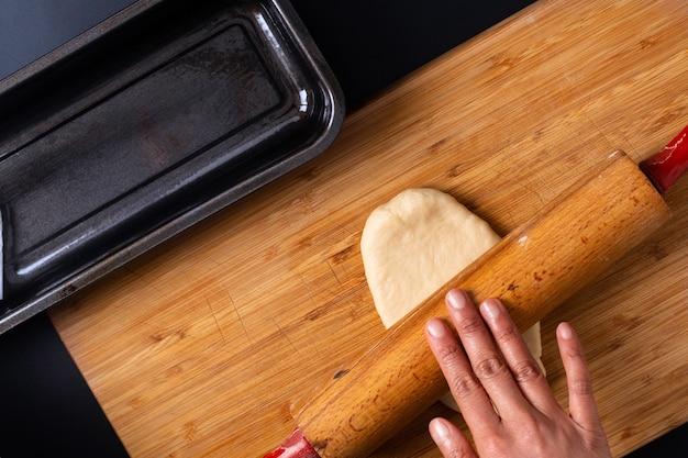 Lebensmittel-backkonzept, das organisches selbst gemachtes weiches milchlaibbrot in der laibwanne auf hölzernem brett macht