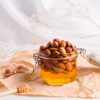 Lebensmittel, die für das immunsystem nützlich sind. honig mit nüssen auf weißem hintergrund
